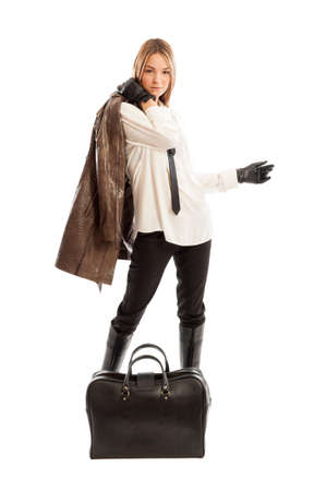 Young fashionable female model holding brown leather jacket over the shoulder and black bag on the floor Stock Photo