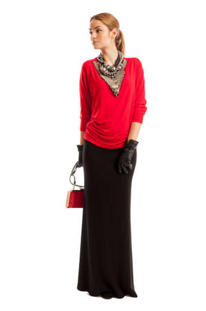 Female model wearing red blouse, long black skirt, smal purse and accessories arround her neck photo
