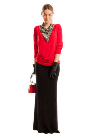Young female model wearing red blouse, long black skirt, smal purse and accessories arround her neck photo