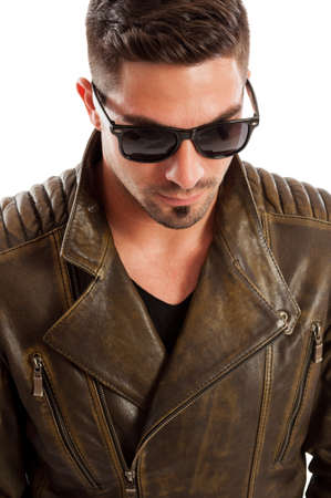 Handsome man wearing leather jacket and sunglasses acting like a bad boy Stock Photo