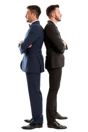 competitive business: Suited and competitive business men standing back to back isolated on white background