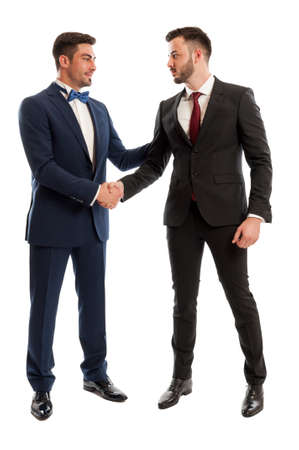 Rich and elegant business people wearing expensive suits and shaking hands photo