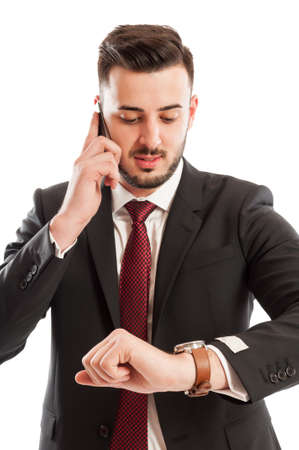 Business man talking on the phone while checking his watch photo