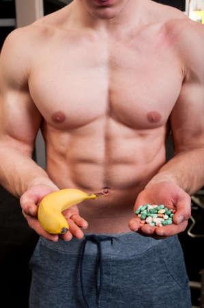 Muscle man choice between natural banana and a hand of pills