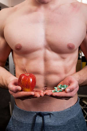 weighs: Muscle man choice between natural red apple and a hand of pills