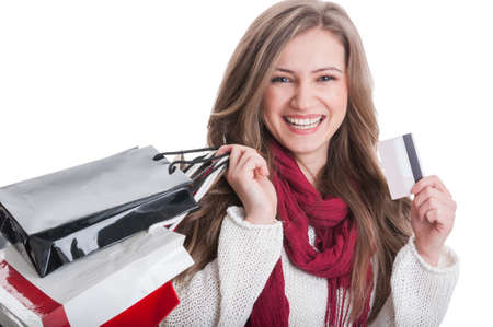 Happy shopping girl holding a credit card and paper bags on white background photo