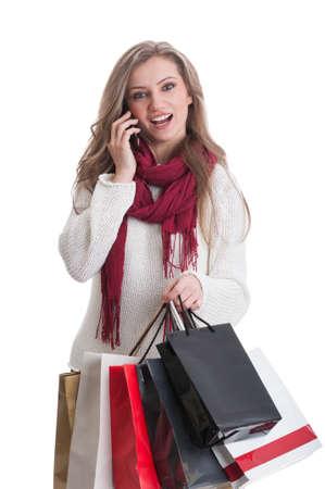 compras compulsivas: Muchacha de compras de hablar por tel�fono y actuar sorprendido mientras holding de color bolsas de la compra de papel
