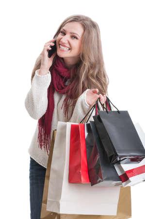 compras compulsivas: Muchacha de compras feliz hablando por el tel�fono y la celebraci�n de bolsas de papel Foto de archivo