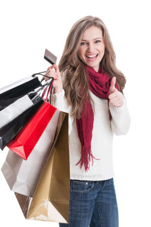 Shopping lady showing thumbsup while holding a debit cared and shopping bags photo