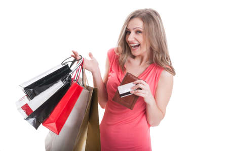 Excited shopping lady holding wallet, credit or debit card and shopping bags photo