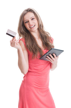 Beautiful and young girl buying online using credit or debit card and a wireless tablet photo