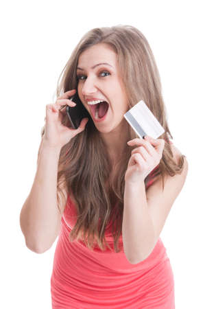 Beautiful blonde excited woman showing a credit or debit card while talking on the phone photo