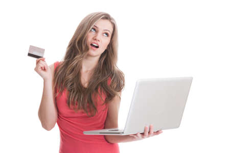 debit card: Beautiful young woman thinking to buy online using credit or debit card while holding a laptop Stock Photo