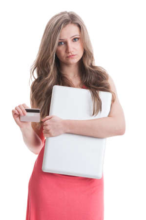 dissapointed: Dissapointed girl holding laptop and debit card. Empty credit card concept on white background Stock Photo