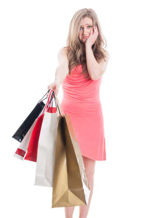 perturbed: Dissapointed young woman holding shopping bags on white background