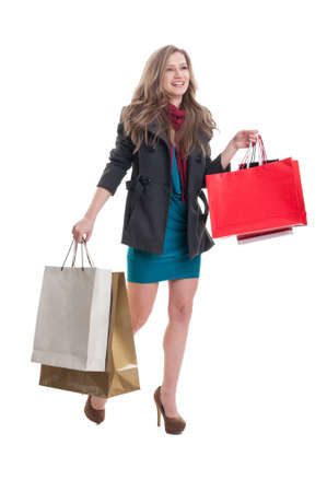 spending full: Beautiful and happy shopping female walking on white background