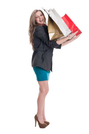 spending full: Smiling shopping girl holding paper bags on her arms on white background
