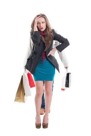 perturbed: Exausted shopping girl having her boyfriend carry the bags on white background