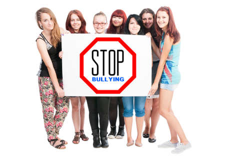card stop: Stop bullying concept written on cardboard held by a bunch of young girl on white background Stock Photo