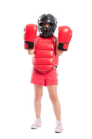 Adorable boxer girl acting mad and wearing full equipment with red boxing gloves and black protection helmet photo