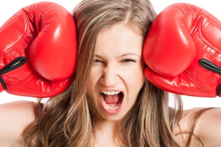 Female model wearing red boxing gloves screaming or shouting expressing madness or angry photo