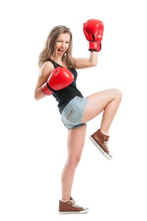 Beautiful female model with boxing gloves screaming and raising hand up like a champion or winner photo