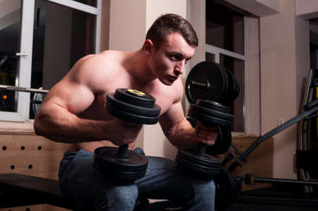 nude male body: Determined body builder in the gym holding two big weights and feeling confident and strong