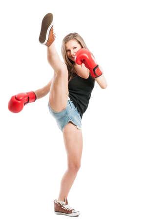 patada: Remate alto con la pierna ejecutado por un combatiente femenino joven sexy y bella con guantes de boxeo rojos Foto de archivo