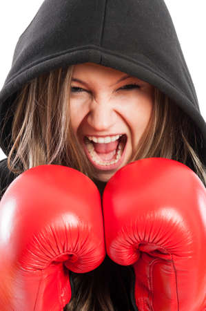 Closeup portrait of an angry but beautiful woman fighter screaming wearing black hoodie and red boxing gloves photo