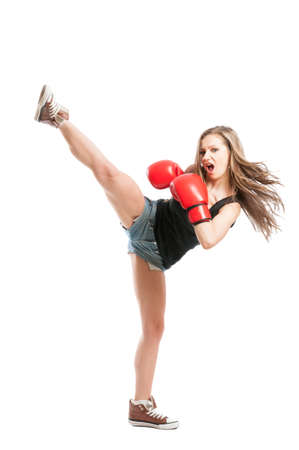 Sexy female fighter kicking high with the leg and wearing red boxing gloves on white background