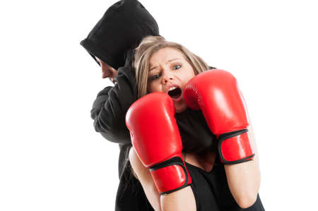 aggressor: Male aggressor grabbing a frightened woman wearing boxing gloves. Female victim concept on white background