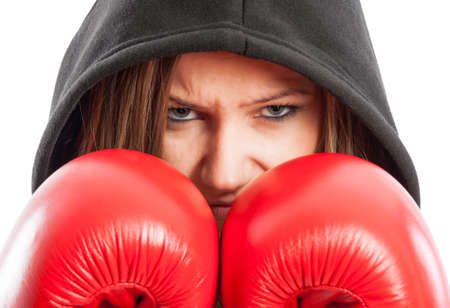Sporty and beautiful female boxer wearing red boxing gloves and black hood photo