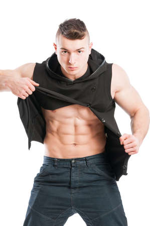 Portrait of a six pack model ripping his black hoodie to show perfect abs
