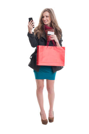 debit card: Shoping lady checking her smartphone and holding red paper bag, wallet and credit or debit card