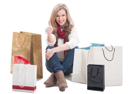 Satisfied shopping woman showing ok or thumb up sitting between shopping bags photo