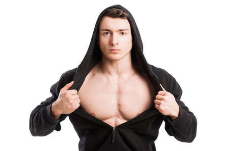 Young and handsome male wearing black hoodie and uncovering his muscular chest photo