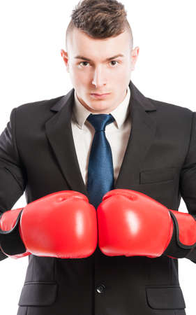 competitive business: Portrait of an aggressive and competitive business man wearing red boxing gloves
