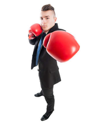 Confident and competitive business man punching the camera with red boxing gloves photo