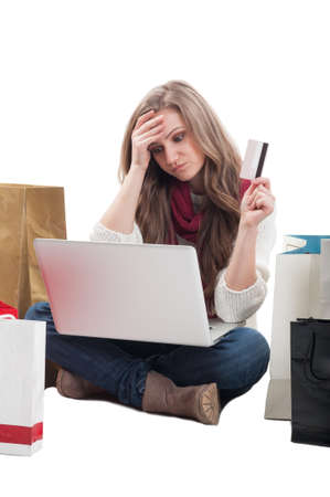 Concerned shopping woman holding empty credit or debit card and looking on the laptop