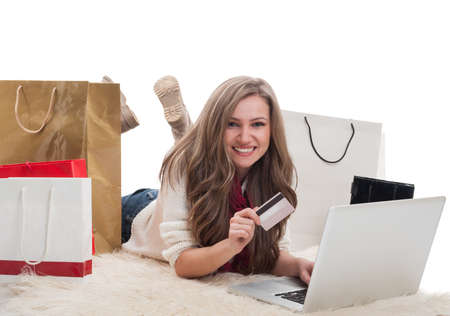 epayment: Happy and satisfied shopping girl using laptop and holdinf credit or debit card surrounded by shopping bags Stock Photo