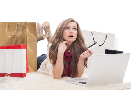 epayment: Shopping female holding card and thinking what to buy online using laptop