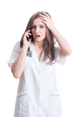 bad news: Woman doctor reveiving bad news on the phone. Concerned female medic concept on white background