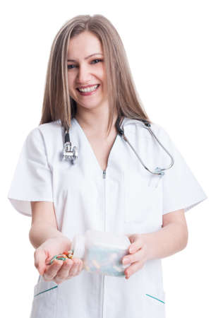 doctor holding pills: Young, happy and smiling woman doctor holding pills and transparent recipient on white background