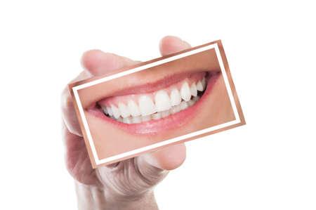dentier: Main tenant une carte avec femme parfaite sourire, prothèse ou les dents isolé sur fond blanc