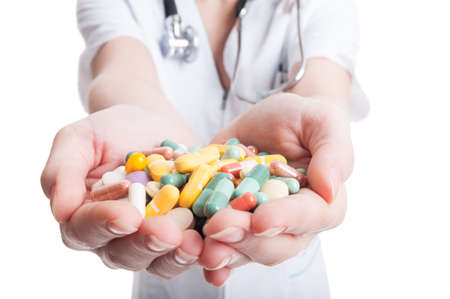 Close up of doctor woman hands holding many pills on white background photo
