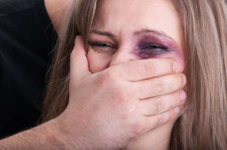 beaten woman: Aggressive man grabbing beaten woman mouth. Domestic violence concept with injuries and bruises