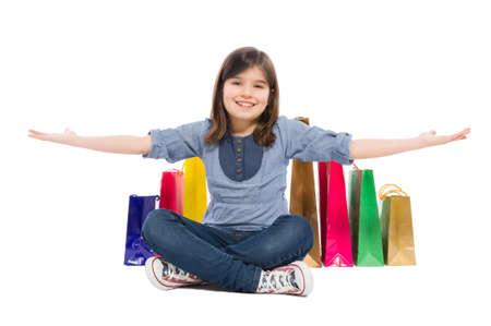 jolie petite fille: Enfant heureuse d'achats ou une jeune fille souriante satisfaits des sacs derrière elle