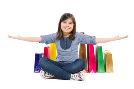 sitting pretty: Happy shopping kid or young girl smiling satisfied of the shopping bags behind her
