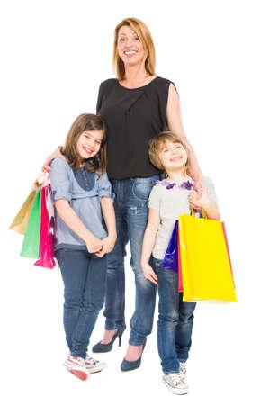 niños de compras: Madre feliz de las compras y las hijas sonriente aislados sobre fondo blanco