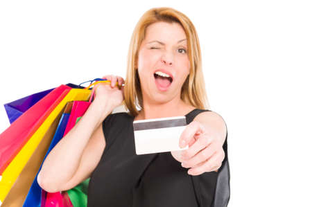 wink: Shopping woman holding credit or debit card and wink to the camera